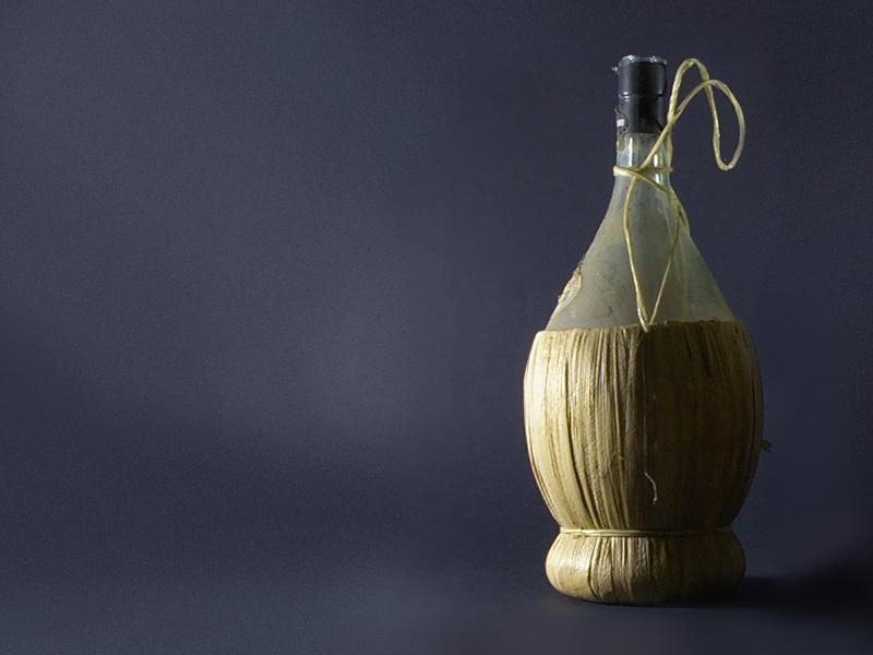 Вино Кьянти в бутылке «фиаска» и плетёной корзине